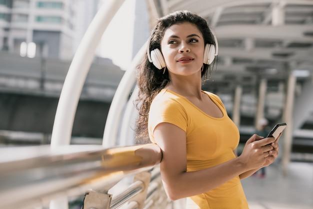 Junge hispanische frau, die die bluetooth kopfhörer hören musik trägt Premium Fotos