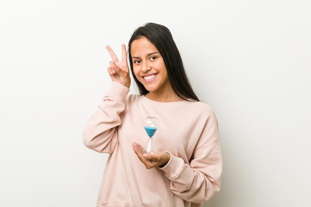 Junge hispanische frau, die eine sanduhr zeigt siegeszeichen und breit lächelt hält. Premium Fotos