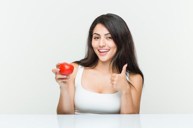 Junge hispanische frau, die eine tomate lächelt und daumen hochhält Premium Fotos