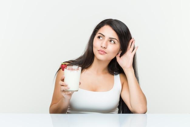 Junge hispanische frau, die einen smoothie hält junge hispanische frau, die einen avocadotoast hält, der versucht, einen klatsch zu hören Premium Fotos