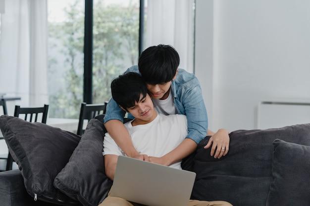Junge homosexuelle paare unter verwendung des computerlaptops am modernen haus. das glückliche asiatische lgbtq + -männer entspannen sich spaß unter verwendung des aufpassenden films der technologie im internet zusammen, während lügensofa im wohnzimmer am haus. Kostenlose Fotos