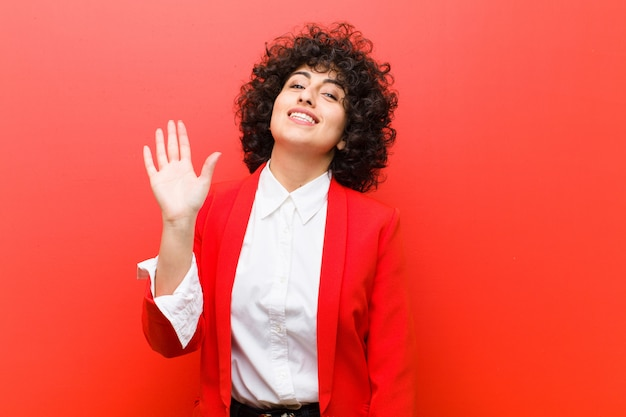 Junge hübsche afrofrau, die glücklich und freundlich lächelt, hand wellenartig bewegt, sie begrüßt und grüßt oder auf wiedersehen sagt Premium Fotos