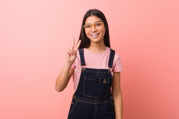 Junge hübsche arabische frau, die einen jeanslatzhose zeigt siegeszeichen und breit lächelt trägt. Premium Fotos
