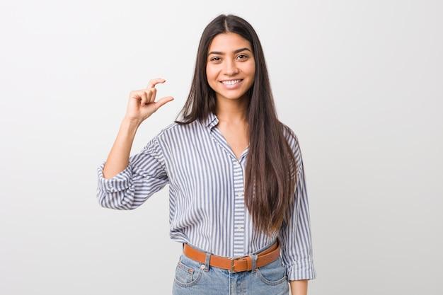 Junge hübsche arabische frau, die etwas wenig mit den zeigefingern hält, lächelt und überzeugt. Premium Fotos