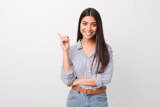 Junge hübsche arabische frau, die mit dem zeigefinger weg freundlich zeigend lächelt. Premium Fotos