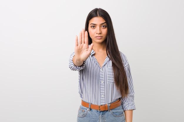 Junge hübsche arabische frau, die mit der ausgestreckten hand zeigt das stoppschild, sie verhindernd steht. Premium Fotos