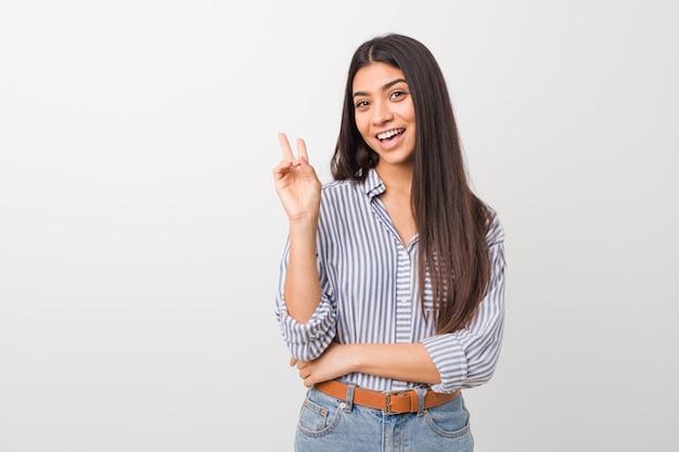 Junge hübsche arabische frau freudig und sorglos, ein friedenssymbol mit den fingern zeigend. Premium Fotos