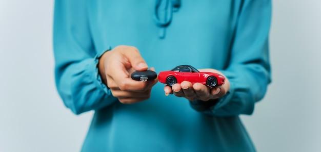 Junge hübsche asiatische frau, die autoschlüssel und autospielzeug beim stehen im studioschuss hält. Premium Fotos