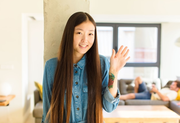 Junge hübsche asiatische frau, die glücklich und fröhlich lächelt, hand winkt, sie begrüßt und begrüßt oder sich verabschiedet Premium Fotos