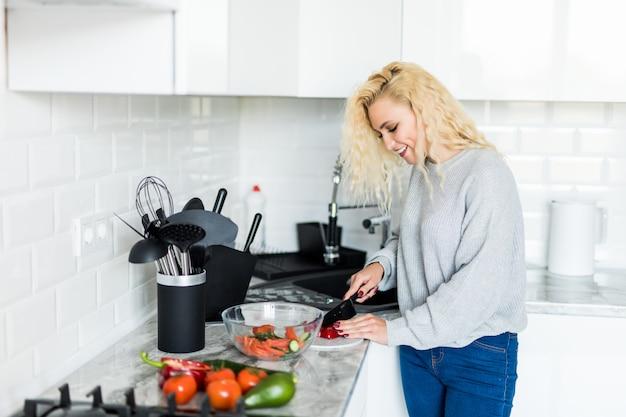 Junge hübsche blonde frau, die gemüse für salat zu hause in der küche schneidet. biolebensmittelkonzept. Kostenlose Fotos