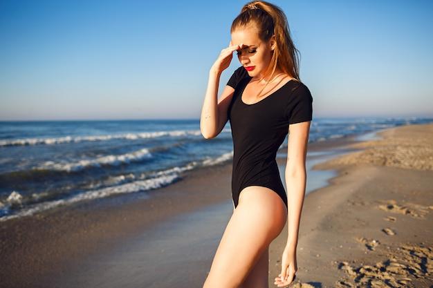 Junge hübsche blonde frau, die schwarzen bikini, schlanken körper trägt, genießt urlaub und hat spaß am strand, lange blonde haare, sonnenbrille und strohhut. allein in der nähe des ozeans Kostenlose Fotos