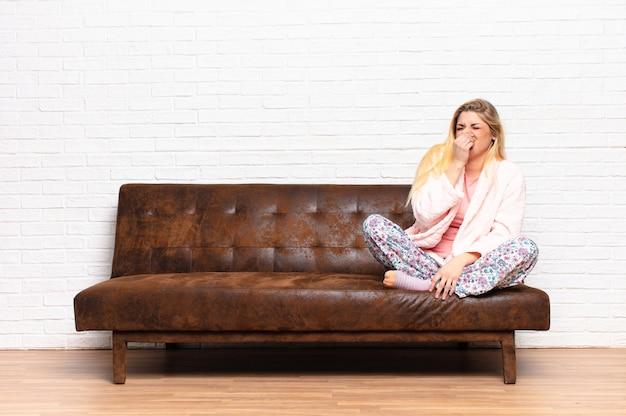 Junge hübsche blonde frau, die sich angewidert fühlt und die nase hält, um einen üblen und unangenehmen gestank zu vermeiden Premium Fotos