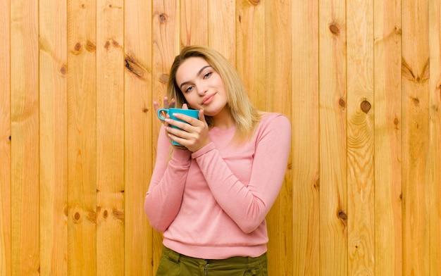 Junge hübsche blondine mit einer kaffeetasse gegen hölzerne wand Premium Fotos