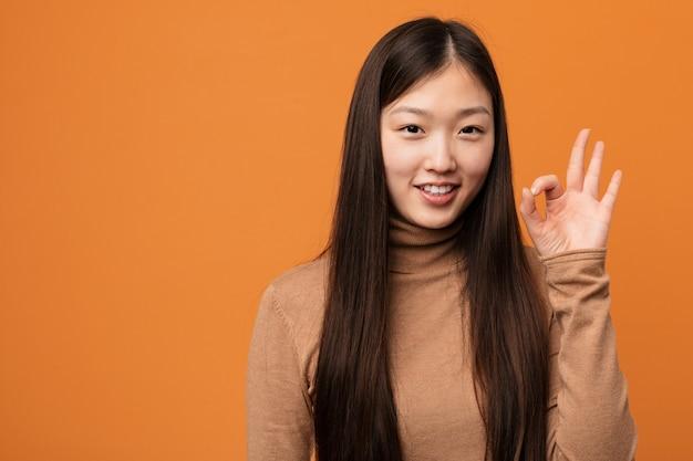 Junge hübsche chinesin nett und überzeugt, okaygeste zeigend. Premium Fotos