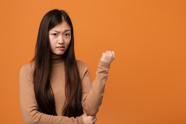Junge hübsche chinesische frau, die sich zurück vom kopf berührt, eine wahl denkt und trifft. Premium Fotos