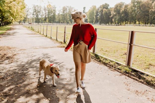 Junge hübsche dame, die mit ihrem hund im park spielt. schöner blonder und weißer labrador, der gute zeit zusammen hat. Kostenlose Fotos