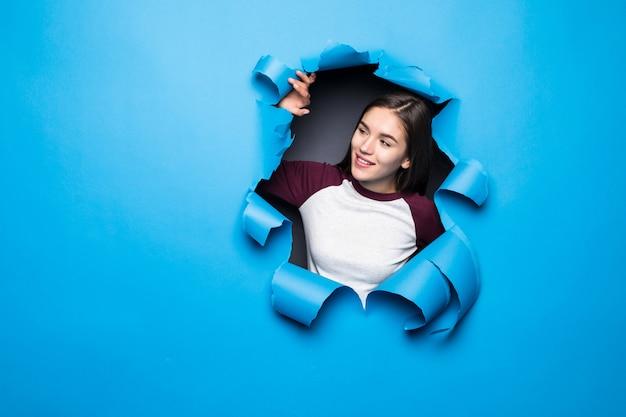 Junge hübsche frau, die durch blaues loch in papierwand schaut. Kostenlose Fotos