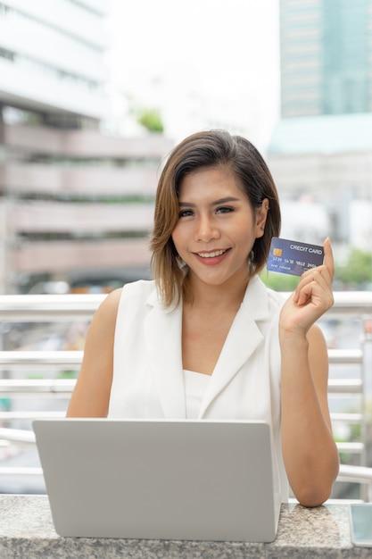 Junge hübsche frau, die kreditkarte für zahlung für online kaufen mit laptop-computer zeigt Kostenlose Fotos