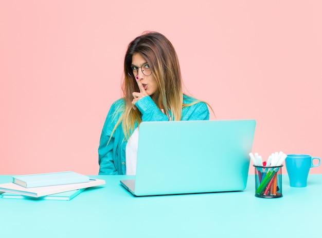 Junge hübsche frau, die mit einem laptop bittet um ruhe und frieden, gestikuliert mit dem finger vor mund, sagt shh oder hält ein geheimnis Premium Fotos