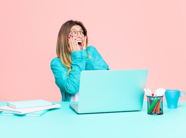 Junge hübsche frau, die mit einem laptop sich fühlt glücklich, aufgeregt und überrascht, schauend zur seite mit beiden händen auf gesicht arbeitet Premium Fotos