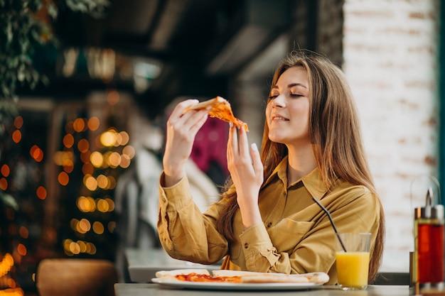 Junge hübsche frau, die pizza an einer bar isst Kostenlose Fotos