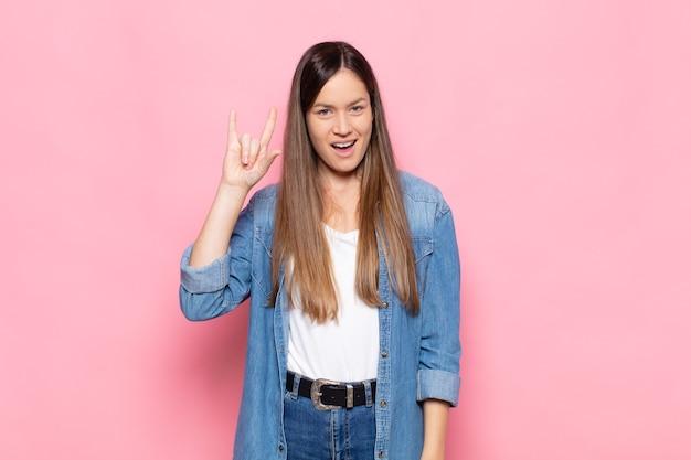 Junge hübsche frau, die sich glücklich, lustig, selbstbewusst, positiv und rebellisch fühlt und mit der hand rock- oder heavy-metal-zeichen macht Premium Fotos