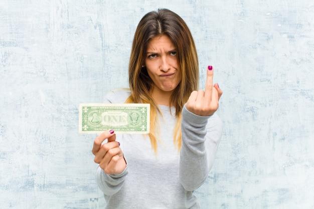 Junge hübsche frau mit banknoten gegen schmutzwand Premium Fotos