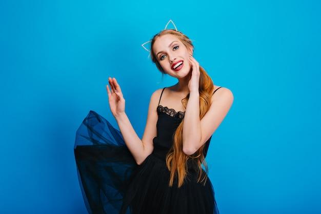 Junge hübsche frau mit dem schönen lächeln, flatterndes schwarzes kleid, posierend. sie hat lange haare, trägt ein stirnband mit katzenohren und ein schönes make-up mit rotem lippenstift. Kostenlose Fotos