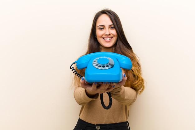 Junge hübsche frau mit einem blauen weinlesetelefon Premium Fotos