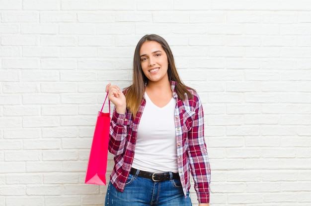 Junge hübsche frau mit einkaufstaschen gegen backsteinmauerbeschaffenheit Premium Fotos