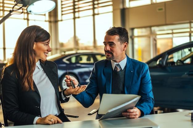 Junge hübsche frau, welche die schlüssel ihres neuwagens empfängt. Premium Fotos