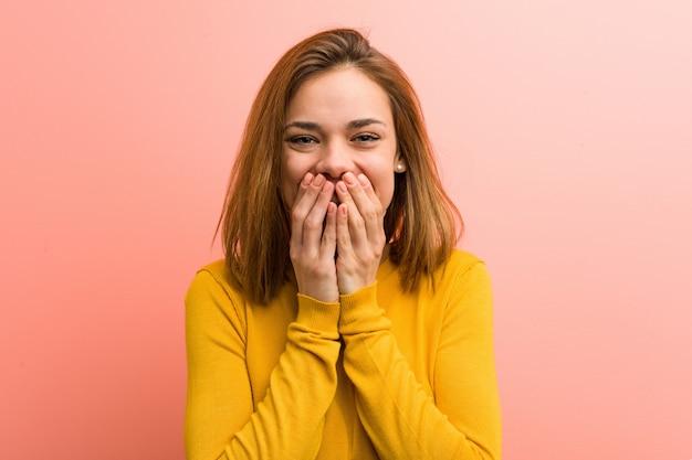 Junge hübsche junge frau, die über etwas lacht und mund mit den händen bedeckt. Premium Fotos