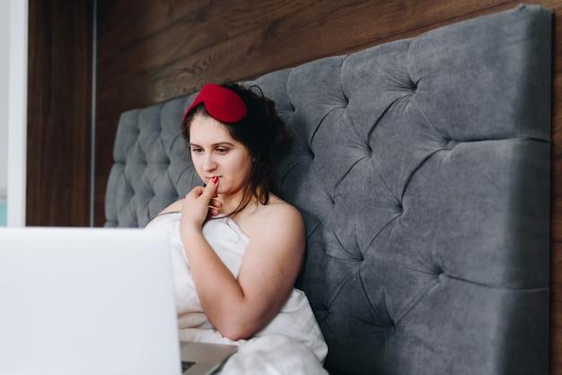 Junge hübsche kaukasische geschäftsfrau, die an ihrem laptop in ihrem bett arbeitet Premium Fotos