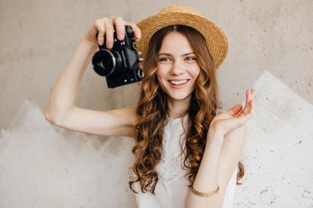 Junge hübsche lächelnde glückliche frau, die weiße bluse trägt, die gegen wand im strohhut sitzt Kostenlose Fotos