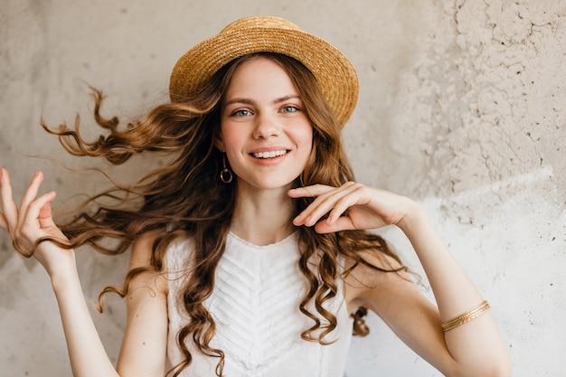 Junge hübsche lächelnde glückliche frau, die weißes hemd trägt, das gegen wand im strohhut sitzt Kostenlose Fotos