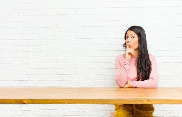 Junge hübsche lateinische frau, die um ruhe und stille bittet, mit dem finger vor mund gestikuliert, shh sagt oder ein geheimes sitzen vor einer tabelle hält Premium Fotos