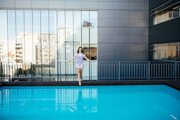 Junge hübsche modesportfrau, die im sommer im freien in heißem wetter im bikini auf pool aufwirft Kostenlose Fotos
