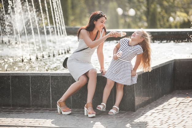 Junge hübsche mutter und ihre tochter haben spaß zusammen in der nähe des brunnens. schöne frau und ihr kleines kind, die eis essen. fröhliche familie, die spaß hat. Premium Fotos