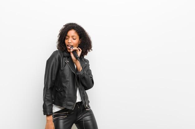 Junge hübsche schwarze frau mit einem mikrofon, das eine lederjacke trägt Premium Fotos