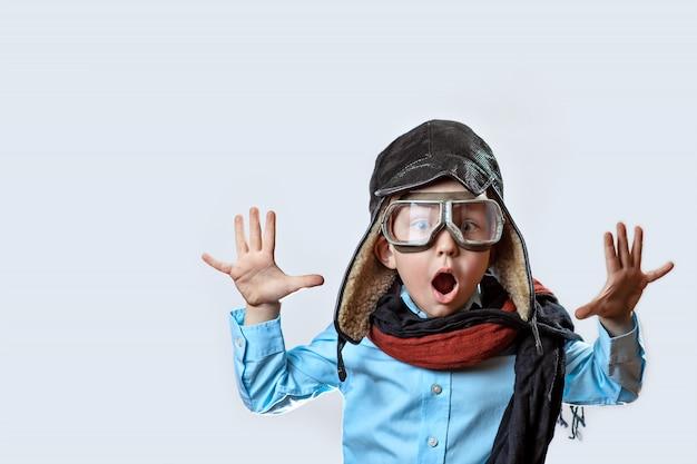 Junge in einem blauen hemd, einer pilotenbrille, einer mütze und einem schal hob die hände auf hellem hintergrund Premium Fotos