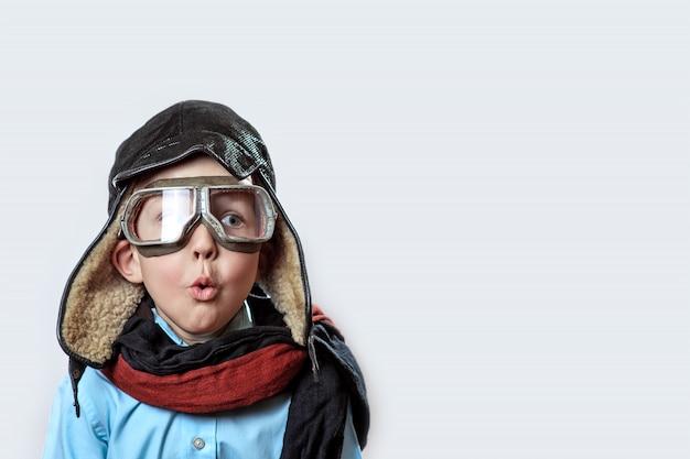 Junge in einem blauen hemd, einer pilotenbrille, einer mütze und einem schal Premium Fotos