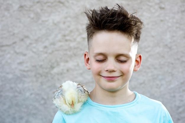 Junge in einem blauen t-shirt mit einem flaumigen huhn schloss seine augen und träumte auf einem unscharfen hintergrund. Premium Fotos