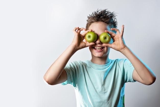 Junge in einem blauen t-shirt setzte zwei grüne äpfel zu seinen augen und lacht auf einem hellen hintergrund Premium Fotos