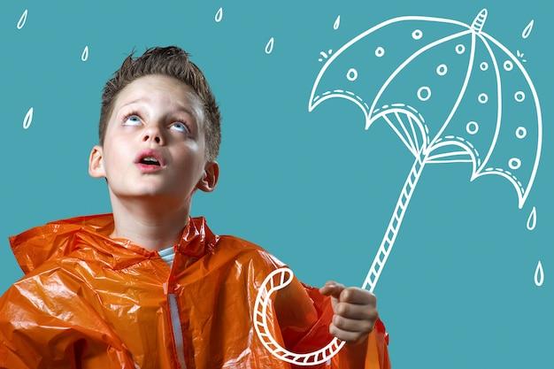 Junge in einem orangefarbenen regenmantel und mit einem bemalten regenschirm steht im regen Premium Fotos