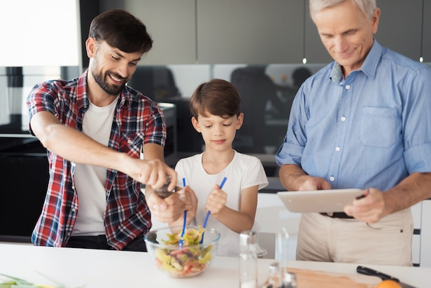 Junge in einem weißen t-shirt mit seinem vater bereiten einen salat zu Premium Fotos