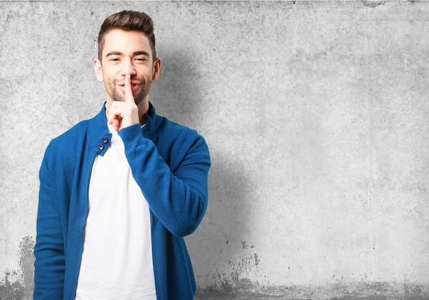 Junge in einer blauen jacke lächelnd und um ruhe bittet Kostenlose Fotos