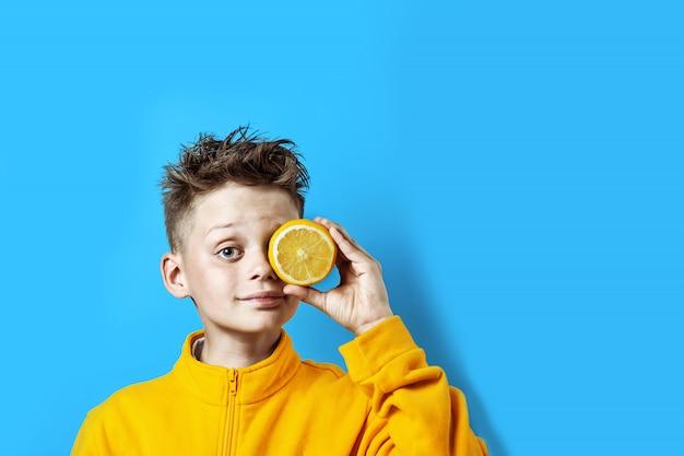 Junge in einer hellen gelben jacke mit einer zitrone in seiner hand auf einem blauen hintergrund Premium Fotos