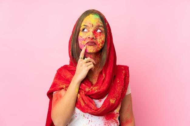 Junge indische frau mit bunten holipulvern auf ihrem gesicht lokalisiert auf rosa wand, die zweifel und denken hat Premium Fotos