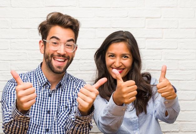Junge indische frau und kaukasische mannpaare nett und aufgeregt, oben lächelnd, daumen hoch, konzept des erfolgs und zustimmung, okaygeste und anheben Premium Fotos