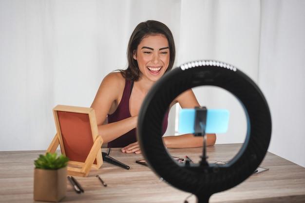Junge influencer-frau, die social-media-videos mit smartphone-kamera beim schminken erstellt Premium Fotos